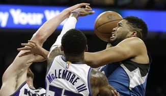Minnesota Timberwolves center Karl-Anthony Towns, right, goes to the basket against Sacramento Kings' Kosta Koufos, left, and Ben McLemore, center, during the first half of an NBA basketball game Monday, Feb. 27, 2017, in Sacramento, Calif. (AP Photo/Rich Pedroncelli)