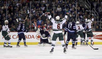 Minnesota Wild's Marco Scandella (6) celebrates after scoring on Winnipeg Jets goalie Connor Hellebuyck (37) during the second period of an NHL hockey game Tuesday, Feb. 28, 2017, in Winnipeg, Manitoba. (Trevor Hagan/The Canadian Press via AP)