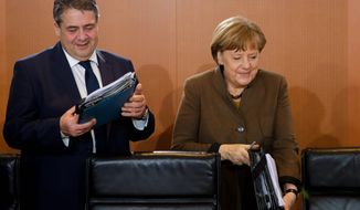 """Foreign Minister Sigmar Gabriel (left), an ally of German Chancellor Angela Merkel (right), said a Berlin military boost could raise fears of German """"military supremacy"""" in Europe at the same time President Trump says NATO members must pay their share. (Associated Press)"""