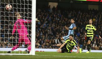 Manchester City's Sergio Aguero, center, scores his side's fourth goal during the English FA Cup soccer match between Manchester City and Huddersfield Town at the Etihad stadium in Manchester, Wednesday, March 1, 2017.(AP Photo/Dave Thompson)