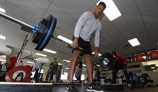 In this Thursday, Feb. 16, 2017, photograph, Air Force wide receiver Jalen Robinette lifts weights as he prepares for the NFL combine, at a workout facility in Centennial, Colo. The 330 players arriving at the NFL's annual combine have been readying for this week's combine in Indianapolis. (AP Photo/David Zalubowski)