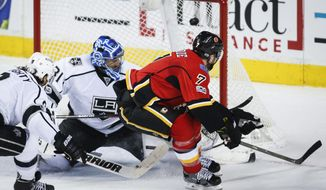 Los Angeles Kings goalie Ben Bishop, left, middle, watches Calgary Flames' T.J. Brodie scores during overtime in an NHL hockey game Tuesday, Feb. 28, 2017, in Calgary, Alberta. (Jeff McIntosh/The Canadian Press via AP)