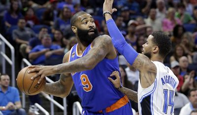 New York Knicks' Kyle O'Quinn, left, looks to pass the ball around Orlando Magic's D.J. Augustin (14) during the first half of an NBA basketball game, Wednesday, March 1, 2017, in Orlando, Fla. (AP Photo/John Raoux)