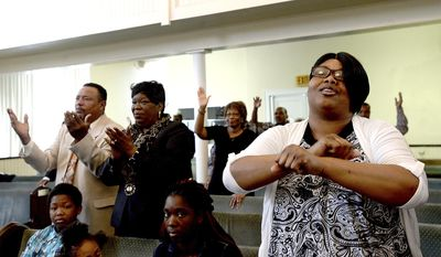 ADVANCE FOR SUNDAY, MARCH 5 AND THEREAFTER - In a Feb. 19, 2017 photo, congregants join in the worship during Sunday morning services at Mount Zion Missionary Baptist Church in Orange, Texas. In honor of Black History Month, part of Rev. C.W. Crawford's message to the congregation was on the role the church has played within the community as the first established Black church in Orange, and the part it continues to play in bettering the lives of those within the community. (Kim Brent/The Beaumont Enterprise via AP)