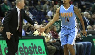 Denver Nuggets guard Gary Harris, right, is congratulated by head coach Michael Malone, left, after making a three point basket against the Milwaukee Bucks during the second half of an NBA basketball game Wednesday, March 1, 2017, in Milwaukee. (AP Photo/Darren Hauck)