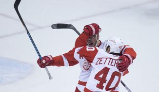 Detroit Red Wings' Justin Abdelkader, back, and Henrik Zetterberg, of Sweden, celebrate Abdelkader's game-winning goal against the Vancouver Canucks during overtime of an NHL hockey game Tuesday, Feb. 28, 2017, in Vancouver, British Columbia. (Darryl Dyck/The Canadian Press via AP)