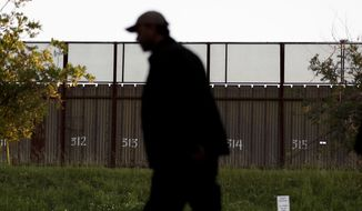 A man passes a section of border fencing that separates Tijuana, Mexico, with San Diego on Tuesday, Feb. 28, 2017, in San Diego. President Donald Trump, signaling a potential shift on a signature issue, indicated Tuesday that he's open to immigration legislation that would give legal status to some people living in the U.S. illegally and provide a pathway to citizenship to those brought to the U.S. illegally as children. (AP Photo/Gregory Bull)