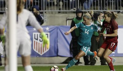 Germany's Anna Blasse (14) tries to get a shot past United States' Alyssa Naeher, foreground, as Tobin Heath (17) defends during the first half of a SheBelieves Cup women's soccer match, Wednesday, March 1, 2017, in Chester, Pa. (AP Photo/Matt Slocum)