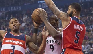 Toronto Raptors forward Serge Ibaka (9) tries to drive between Washington Wizards guard Bradley Beal (3) and Markieff Morris during the first half of an NBA basketball game, Wednesday, March 1, 2017 in Toronto. (Chris Young/The Canadian Press via AP)