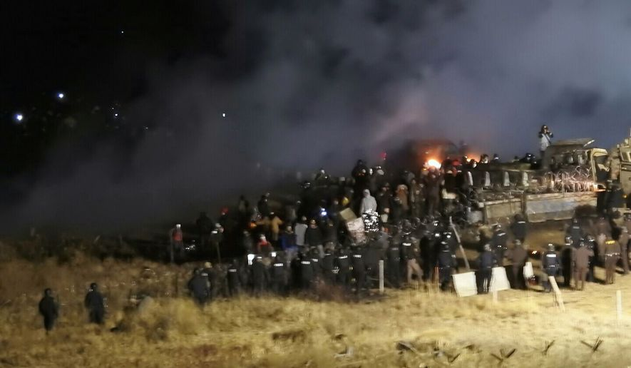 FILE - In this Nov. 20, 2016, file photo, provided by Morton County Sheriff's Department, law enforcement and protesters clash near the site of the Dakota Access pipeline near Cannon Ball, N.D. Prosecutors have withdrawn a subpoena for Steve Martinez, a pipeline opponent from Williston, N.D., who had been ordered to testify about the violent clash in November. (Morton County Sheriff's Department via AP)