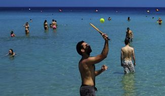 """FILE - In this Sunday, May 25, 2014 file photo, a man plays rackets as other tourists enjoy the sea at """"Konnos"""" beach near the famous coastal resort of Ayia Napa in the eastern Mediterranean island of Cyprus. Cyprus' top tourism official says on Thursday, March 2, 2017, tourist arrivals are expected to increase by another 5 percent this year, on top of a record-setting 2016 that saw almost 3.2 million holidaymakers travel to the east Mediterranean island. (AP Photo/Petros Karadjias, File)"""