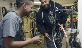 In a Thursday, Feb. 16, 2017 photo, DaiQuan Medley, 19, rushes in to disassemble a bike wheel during a race with other youth mechanics as Sterling Stone, right, lets go of the wheel at Gearin' Up Bicycles in northeast Washington, D.C. Stone, is the executive director of the non-profit bike shop, founded in 2012, that gives career development opportunities and teaches essential workplace skills to teenagers from underserved communities.  (Rebecca Droke/Pittsburgh Post-Gazette via AP)