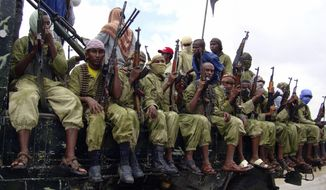 FILE - In this Oct. 30, 2009 file photo, al-Shabab fighters sit on a truck as they patrol in Mogadishu, Somalia. The African Union (AU) peacekeeping mission in Somalia says at least 57 members of the al-Shabab extremist group have been killed Thursday, March 2, 2017 after AU and Somali forces attacked one of its camps. (AP Photo/Mohamed Sheikh Nor, File)