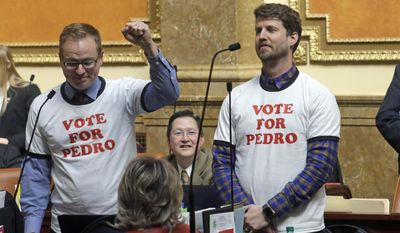 """Actor and producer Jon Heder, right, stands next to Rep. Jeremy Peterson, R-Ogden, raising his fist in front of the Utah House of Representatives at the Utah State Capitol on Thursday, March 2, 2017, in Salt Lake City. The star of 2004 hit movie """"Napoleon Dynamite"""" is telling lawmakers that Utah's film tax incentives are vital to luring productions to the state. (AP Photo/Rick Bowmer)"""