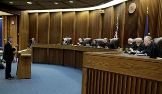 FILE- In this Sept. 21, 2016 file photo, school district attorney Alan Rupe, left, presents his arguments in a school funding case at the Kansas Supreme Court in Topeka, Kan.  Kansas' highest court on Thursday, March 2, 2017, ordered the state to increase its spending on public schools, which could further complicate the state's dire budget problems and increase pressure to undo large tax cuts championed by Republican Gov. Sam Brownback. (AP Photo/Charlie Riedel, File)
