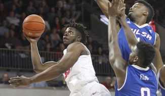 SMU forward Semi Ojeleye, left, puts up a shot while being pressured by Tulsa forwards Martins Igbanu (1) and Junior Etou (0) during the first half of an NCAA college basketball game, Thursday, March 2, 2017, in Dallas. (AP Photo/Tim Sharp)