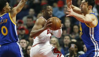 Chicago Bulls guard Dwyane Wade, center, looks to pass between Golden State Warriors guard Patrick McCaw, left, and center Zaza Pachulia during the first half of an NBA basketball game Thursday, March 2, 2017, in Chicago. (AP Photo/Nam Y. Huh)