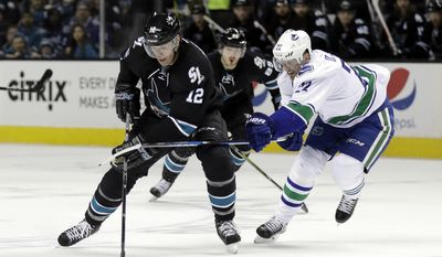 San Jose Sharks' Patrick Marleau (12) is defended by Vancouver Canucks' Daniel Sedin (22) during the first period of an NHL hockey game Thursday, March 2, 2017, in San Jose, Calif. (AP Photo/Marcio Jose Sanchez)