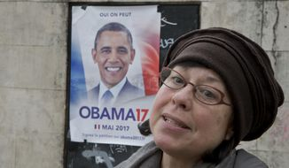 """American Sarah Wachter speaks to The Associated-Press during an interview next to a campaign poster with the picture of former U.S. President Barack Obama reading in French """"yes we can"""" in Paris, Friday, March 3, 2017. An online petition urging Barack Obama to join the French presidential race has attracted more than 45,000 signatures in 10 days. (AP Photo/Michel Euler)"""