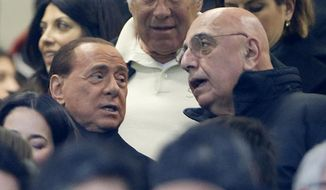 FILE - In this  Jan. 31, 2016 file photo, AC Milan president Silvio Berlusconi, left, is flanked by vice president Adriano Galliani during a Serie A soccer match between AC Milan and Inter Milan, at the San Siro stadium in Milan, Italy. The sale of AC Milan to a group of Chinese investors was again delayed on Friday, March 3, 2017. (AP Photo/Luca Bruno)