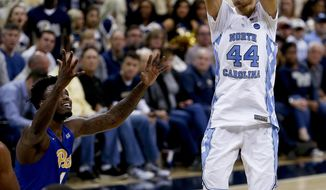 FILE - In  this Feb. 25, 2017, file photo, North Carolina's Justin Jackson (44) shoots for three over Pittsburgh's Jamel Artis (1) during the second half of an NCAA college basketball game, in Pittsburgh. Jackson has expanded his 3-point range so well that he's made himself an ACC player of the year candidate for No. 5 North Carolina entering Saturday's rivalry game with No. 17 Duke. (AP Photo/Keith Srakocic, File)