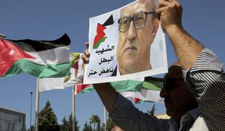FILE - In this Monday, Sept. 26, 2016, file photo, relatives of Jordanian writer Nahed Hattar hold up signs protesting his death, in front of Jordanian Prime Ministry in Amman, Jordan. Nahad Hattar, the writer, had been on trial for posting a cartoon deemed offensive to Islam on social media when an assailant killed him outside the courthouse. The shooter was a former mosque prayer leader motivated by anger over the cartoon, officials said at the time. (AP Photo/Raad Adayleh)