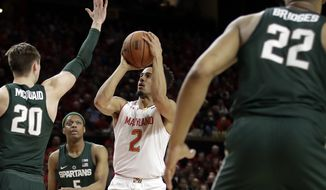 Maryland guard Melo Trimble (2) shoots against Michigan State guards Matt McQuaid (20), Cassius Winston (5) and Miles Bridges in the second half of an NCAA college basketball game, Saturday, March 4, 2017, in College Park, Md. Maryland won 63-60. (AP Photo/Patrick Semansky)