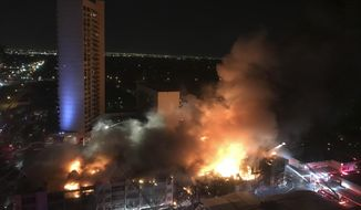 A fire burns in a four-story condominium building in Dallas, early Saturday, March 4, 2017.  Dallas Fire-Rescue spokesman Jason Evans said in a statement early Saturday that residents of the building calmly left just before 11:30 p.m. Friday because of smoke, shortly before flames erupted.Evans says firefighters worked into the early hours to put out the fire, which slowly burned from one area toward the front of the building. (AP Photo/Mary Clare Jalonick)