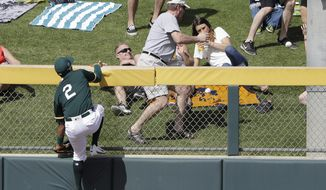 Oakland Athletics' Khris Davis watches a three-run home run by Cleveland Indians' Erik Gonzalez during the third inning of a spring training baseball game Saturday, March 4, 2017, in Mesa, Ariz. (AP Photo/Darron Cummings)