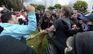 Anti-Trump protesters try to take a large piece of wood away from a Trump supporter at a rally for President Donald Trump at Martin Luther King Jr. Civic Center Park in Berkeley, Calif., Saturday, March 4, 2017. Berkeley Police officers in riot gear arrested at least one person at the rally that attracted hundreds of pro-Trump supporters and opponents at a park less than a mile from the University of California, Berkeley campus.  (Dan Honda/East Bay Times via AP)