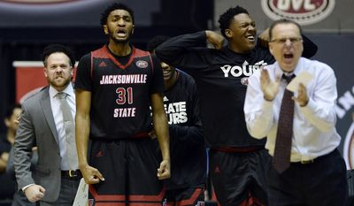 Jacksonville State forward Christian Cunningham (31), guard Andre Statam, second from right, and head coach Ray Harper, right, celebrate after a score during the second half of an NCAA college basketball game against Tennessee-Martin in the championship of the Ohio Valley Conference basketball tournament Saturday, March 4, 2017, in Nashville, Tenn. (AP Photo/Mark Zaleski)