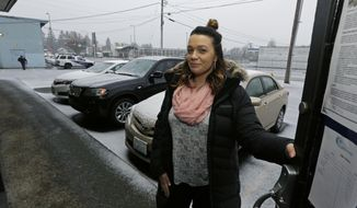 In this photo taken Feb. 27, 2017, Jessica Wolfe poses for a photo in the doorway of The Genesis Project, a drop-in center for victims of sex trafficking in SeaTac, Wash. Wolfe, who was forced into sex trafficking shortly after her 19th birthday is now struggling to find housing and a job after background checks find her prostitution convictions, but a measure passed last week in the Washington state Senate could rewrite current law to make it easier for victims of trafficking to vacate prostitution convictions. (AP Photo/Ted S. Warren)