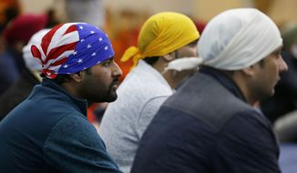 """A man wears a head covering with the stars and stripes of a U.S. flag as he attends Sunday services at the Gurudwara Singh Sabha of Washington, a Sikh temple in Renton, Wash., Sunday, March 5, 2017, south of Seattle. Authorities said a Sikh man said a gunman shot him in his arm Friday, March 3, 2017, as he worked on his car in the driveway and told him """"go back to your own country."""" Sikhs have previously been the target of assaults in the U.S. After the Sept. 11, 2001, attacks, as the backlash that hit Muslims around the country expanded to include those of the Sikh faith. (AP Photo/Ted S. Warren)"""