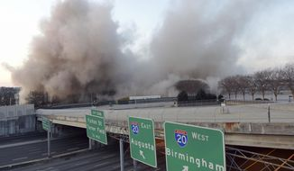 A dust cloud rises after demolition crews brought down the old state archives building shortly after 7 am Sunday, March 5, 2017, in a controlled implosion, in Atlanta. The 14 story state archives building was about 50 years old and was imploded to make way for a new state courts building. Gov. Nathan Deal has budgeted about $105 million in next year's budget for the new state courts building. (Kent D. Johnson/Atlanta Journal-Constitution via AP)