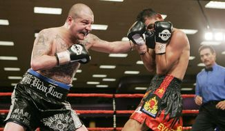 FILE - In this Feb. 23, 2007, file photo, five-time world champion Johnny Tapia, left, connects with Evaristo Primero in the ninth round of a 10-round junior welterweight bout at Isleta Pueblo, N.M. A court-ordered DNA test shows a man who has long claimed to be the father of the late boxing champ Tapia is not his dad after all, in the latest saga involving the troubled boxer after his death. The Albuquerque Journal reports Thursday, March 2, 2017, a copy of the test results obtained by the newspaper indicates conclusively that Jerry Padilla is not Tapia's biological father. (AP Photo/Jake Schoellkopf, File)