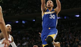 Golden State Warriors guard Stephen Curry (30) goes up for a layup as New York Knicks forward Carmelo Anthony, left, watches from the floor in the first half of an NBA basketball game at Madison Square Garden in New York, Sunday, March 5, 2017. (AP Photo/Kathy Willens)