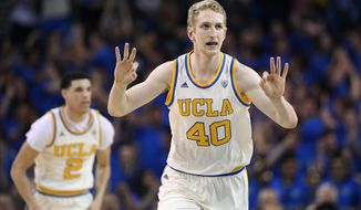 UCLA center Thomas Welsh, right, gestures after scoring as guard Lonzo Ball runs behind during the first half of the team's NCAA college basketball game against Washington State, Saturday, March 4, 2017, in Los Angeles. (AP Photo/Mark J. Terrill)