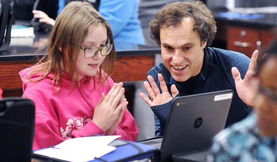 In a Thursday March 2, 2017 photo, Highland Middle School sixth-grader Aliyah Brewer reacts with Highland language arts instructional coach Joe Melo as he helps her find what she is looking for online from the Anderson Public Library on her school-assigned Chromebook, in Anderson, Ind. Highland students are learning how to use their new e-cards to access the public library's resources through a partnership program between the school and library. (John P. Cleary/The Herald-Bulletin via AP)