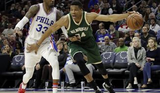Milwaukee Bucks' Giannis Antetokounmpo, right, dribbles past Philadelphia 76ers' Robert Covington during the first half of an NBA basketball game, Monday, March 6, 2017, in Philadelphia. (AP Photo/Matt Slocum)