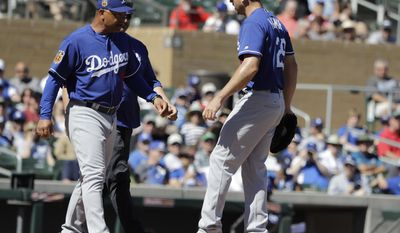 Los Angeles Dodgers manager Dave Roberts talks with starting pitcher Scott Kazmir during the second inning of a spring training baseball game against the Colorado Rockies, Monday, March 6, 2017, in Scottsdale, Ariz. (AP Photo/Darron Cummings)