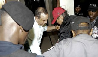 FILE - In this Jan. 28, 2017, file photo, Panamanian ex-dictator Manuel Antonio Noriega, wearing a red baseball cap, arrives after being placed under house arrest for three months in Panama City. Noriega has been hospitalized to undergo surgery to remove a benign tumor from his brain. Thays Noriega, one of his daughters, said surgery was scheduled for Tuesday, March 6. (AP Photo/Arnulfo Franco, File)