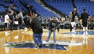 Minnesota Timberwolves' Andrew Wiggins, back right, practices as Target Center workers wipe down the wet basketball floor prior to the NBA basketball game against the Portland Trail Blazers Monday, March 6, 2017, in Minneapolis. High humidity in Minneapolis and condensation from ice underneath the basketball court for upcoming ice-centered events contributed to the wet floor. (AP Photo/Jim Mone)