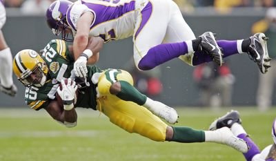 FILE - In this Nov. 11, 2007, file photo, Green Bay Packers running back Ryan Grant (25) is hit by Minnesota Vikings linebacker Chad Greenway (52) during the first half of an NFL football game in Green Bay, Wis. Greenway is retiring. The team says Greenway will announce his retirement at a news conference Tuesday, March 7, 2017, at Vikings headquarters. The 34-year-old Greenway played 11 seasons and appeared in 156 career games with 144 starts for Minnesota. He ranks fourth in franchise history with 1,334 career tackles.(AP Photo/Mike Roemer, file)