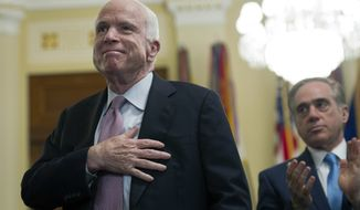 Sen. John McCain, R-Az., places his hand over his heart, while Department of Veterans Affairs Secretary David Shulkin watches, after he addressed the House Veterans' Affairs Committee on Department of Veterans Affairs community care program, on Captiol Hill in Washington, Tuesday, March 7, 2017. (AP Photo/Cliff Owen)