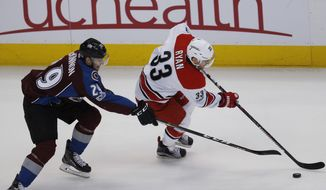 Colorado Avalanche center Nathan MacKinnon, left, pursues Carolina Hurricanes center Derek Ryan as he drives down the ice with the puck in the first period of an NHL hockey game, Tuesday, March 7, 2017, in Denver. (AP Photo/David Zalubowski)