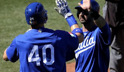 Italy's Brandon Nimmo and Daniel Descalso high five after scoring on a base hit by teammate Francisco Cervelli against the Chicago Cubs during the third inning of a exhibition game, Tuesday, March 7, 2017, in Mesa, Ariz. (AP Photo/Matt York)