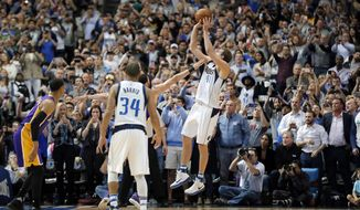 Dallas Mavericks' Devin Harris (34) watches as Dirk Nowitzki (41) of Germany takes a shot that sinks giving Nowitzki his 30,000th career point in the first half of an NBA basketball game against the Los Angeles Lakers in Dallas, Tuesday, March 7, 2017. (AP Photo/Tony Gutierrez)