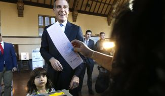 Los Angeles Mayor Eric Garcetti casts his election ballot with his daughter Maya in Los Angeles, on Tuesday, March 7, 2017. Garcetti is looking for a return trip to City Hall and faces 10 little-known challengers. The 46-year-old Democrat is often mentioned as a likely candidate for higher office, and the outcome could provide a springboard for future campaigns or raise doubts about the depth of his appeal. (AP Photo/Nick Ut)