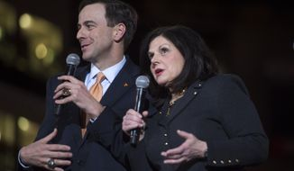 FILE - In this Thursday, March 2, 2017 file photo, New University of Tennessee athletic director John Currie and new University of Tennessee Chancellor Beverly Davenport speak on stage during a ceremony introducing Currie in Thompson-Boling Arena in Knoxville, Tenn. After giving away about 60 orange ties when he left Tennessee in 2009, new Volunteers athletic director John Currie must rebuild his wardrobe now that he's back. But he says the lesson he learned during his time away from Knoxville as Kansas State's athletic director should help him quite a bit in his new job. (Caitie McMekin/Knoxville News Sentinel via AP, File)