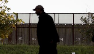 A man passes a section of border fencing that separates Tijuana, Mexico, with San Diego on Tuesday, Feb. 28, 2017, in San Diego. (Associated Press) **FILE**